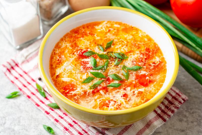 Traditional chinese egg drop soup with tomato and green onion in bowl on gray stone background stock images
