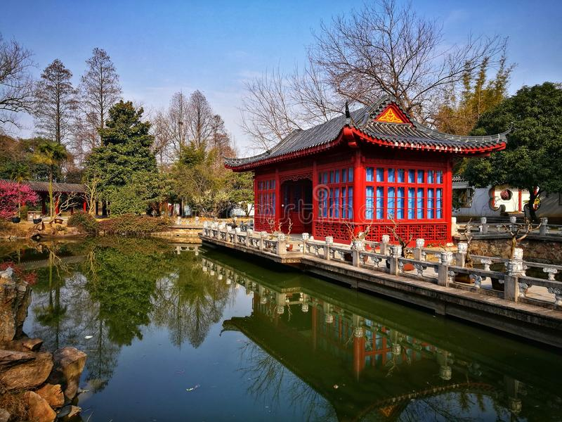 Traditional Chinese garden under blue sky. Traditional Chinese garden with Pavillion,stone bridge and trees stock image