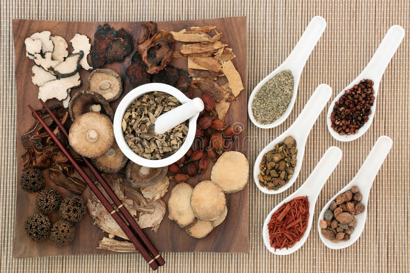 Traditional Chinese Herbal Medicine. Selection on a maple wood board with chopsticks and mortar with pestle and in china spoons on bamboo background stock photos