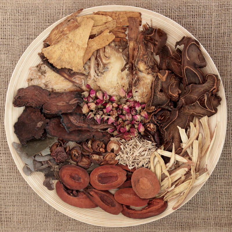 Chinese Herbal Medicine. Traditional chinese herbal medicine selection on a round wooden bowl over hessian background royalty free stock image