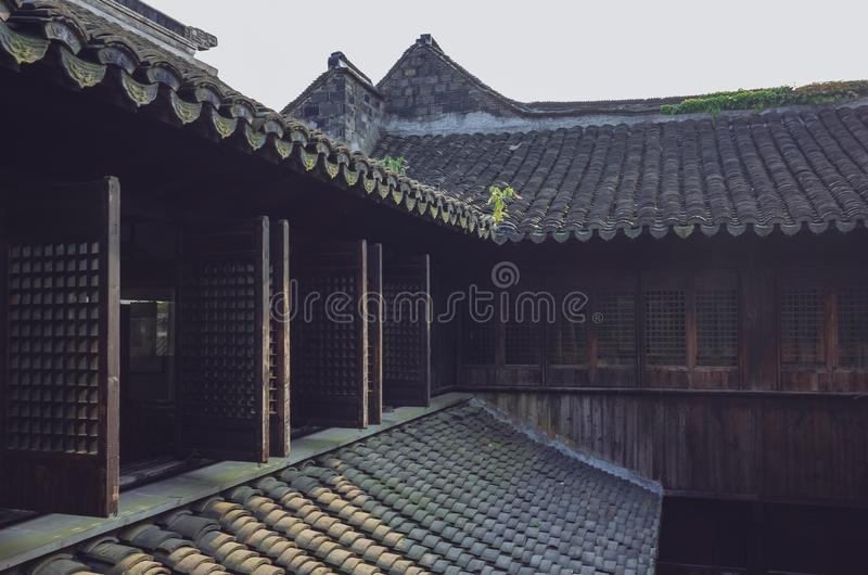 Traditional Chinese houses with windows and rooftops with black roof tiles, in the old town of Xitang, China. Traditional Chinese houses with open windows and stock image