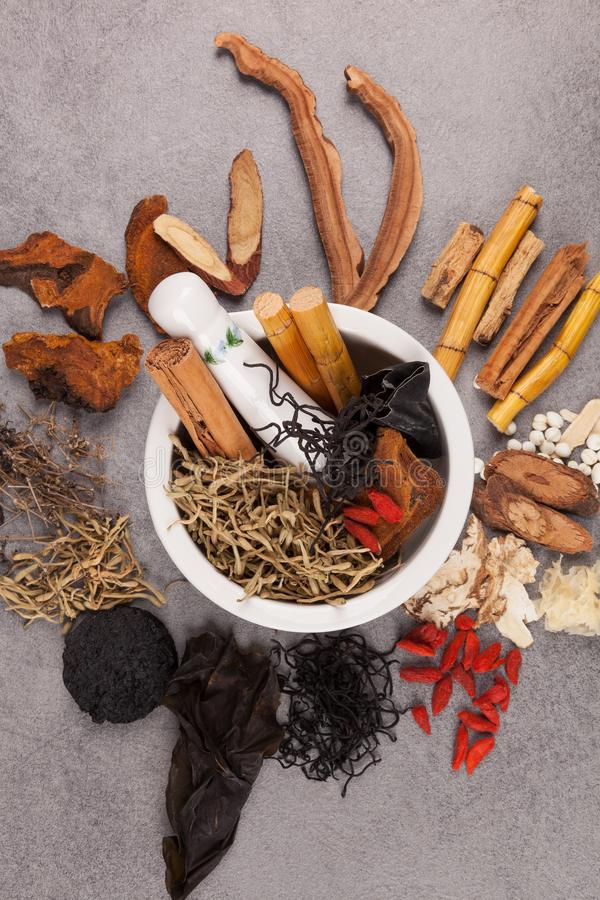 Different kind of Chinese herbal on gray background. Traditional chinese medicine and mortar on gray background royalty free stock photography