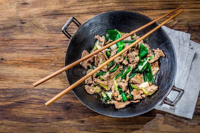 Traditional chinese mongolian beef stir fry in chinese cast iron wok with cooking chopsticks, wooden background. Top. View, copy space stock photo