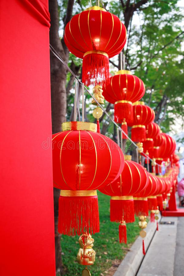 Traditional Chinese Red Nylon Outdoor Vintage Hanging Pendant Light Lanterns with golden tassels decoration adorning street lights. Buildings and shops for stock photos