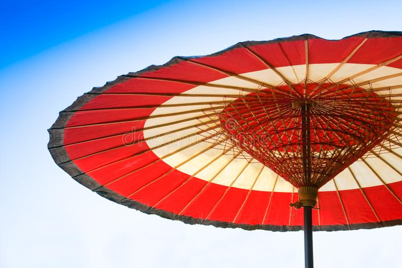 Traditional Chinese red and white oiled-paper umbrella on blue sky stock photos