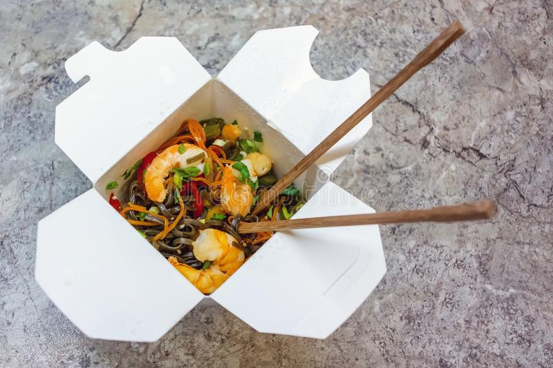 Traditional Chinese takeaway fast food - buckwheat soba noodles with vegetables and shrimps packed in a cardboard box stock photos