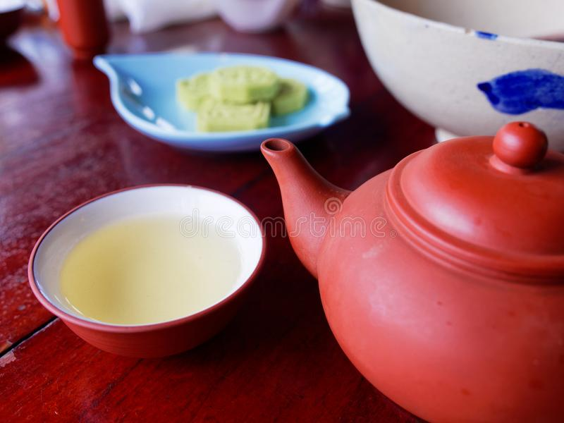 Traditional chinese tea set compose of cup of tea, teapot, and snack on wooden background royalty free stock images