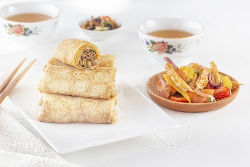 Traditional Chinese tortillas filled - bings in a plate on a white background, salads, Dam Sam snacks and cups stock photography