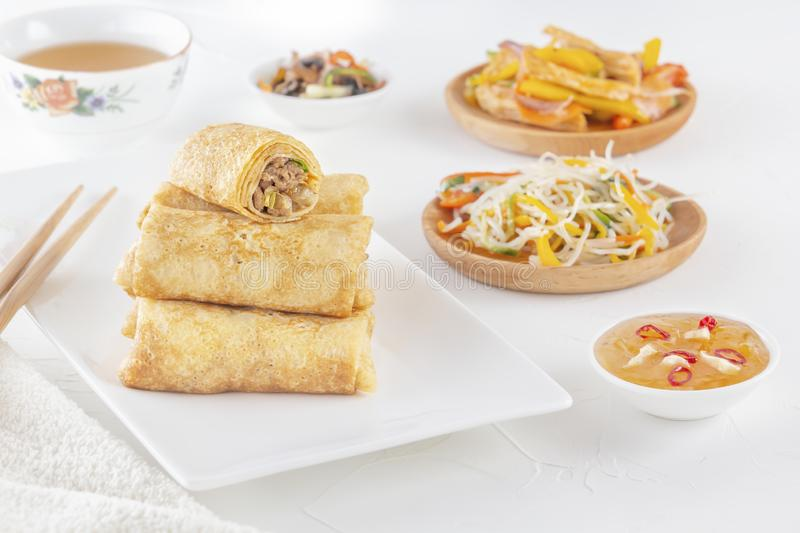 Traditional Chinese tortillas filled - bings in a plate on a white background, salads, Dam Sam snacks and cup of tea. royalty free stock images