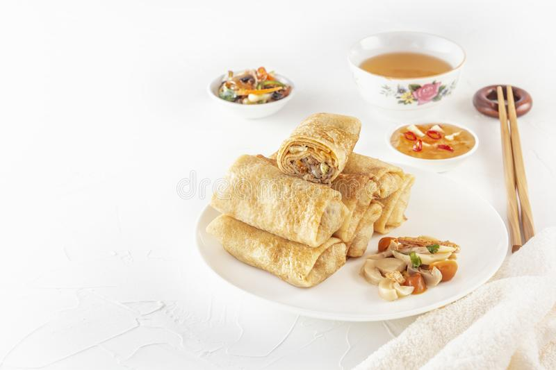 Traditional Chinese tortillas filled - bings in a plate on a white background, salads, Dam Sam snacks and cup of tea. stock photo
