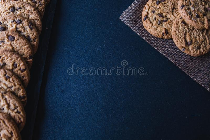 Traditional chocolate chip cookies on a chalkboard table. Top view of cooking course poster background - layout with free text stock photos