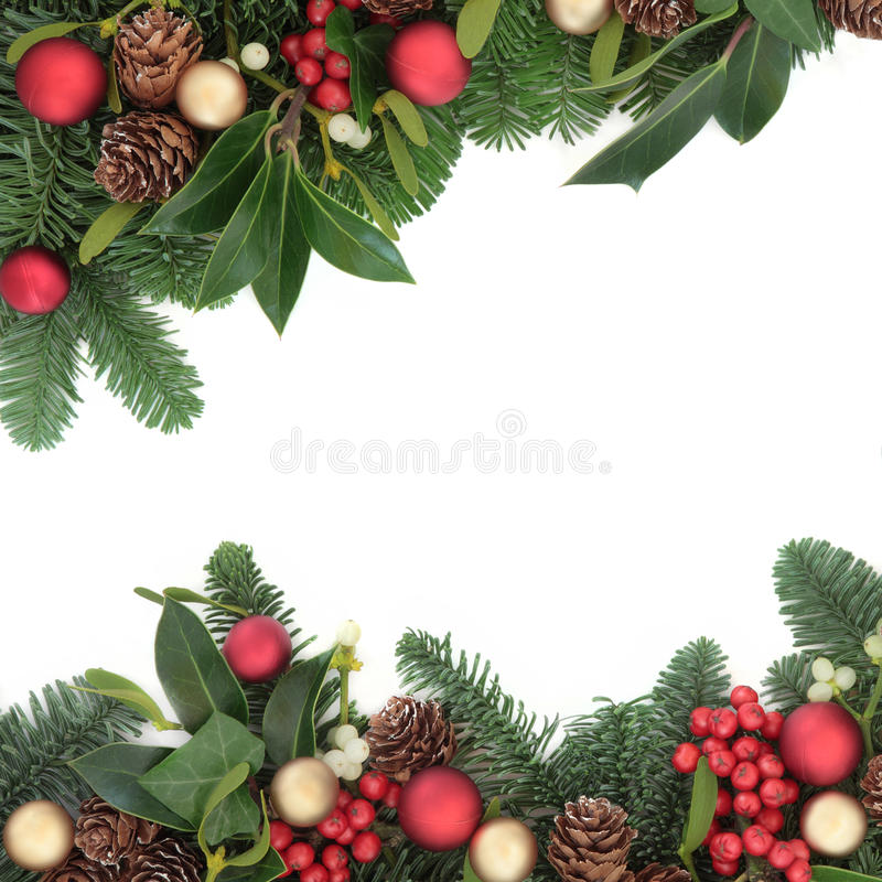 Traditional Christmas Border. Christmas background floral border with bauble decorations, holly, ivy, mistletoe, pine cones and fir over white with copy space royalty free stock photography