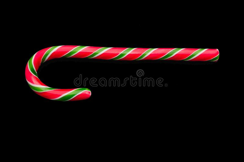 Traditional christmas caramel candy cane isolated on a black background. Winter Holiday festive greeting card with copy space for stock photos