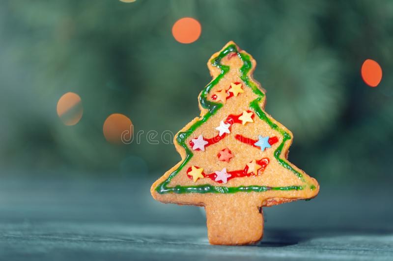 Traditional Christmas cookie in the shape of a man on a background of the Christmas tree. Gray wooden table, free space for text royalty free stock image
