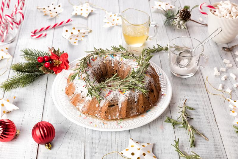 Traditional Christmas fruit cake on a white wooden table. Homemade pudding with festive decorations, candy canes royalty free stock image