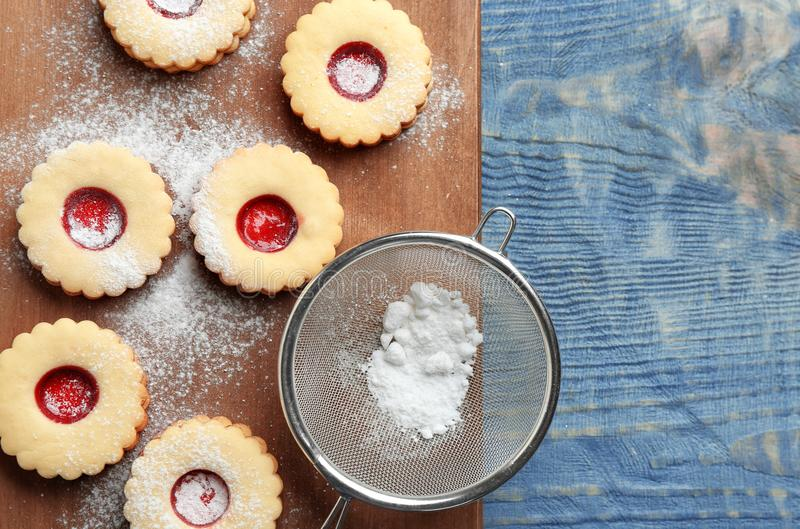 Traditional Christmas Linzer cookies with sweet jam. And sugar powder on wooden background, top view stock photo