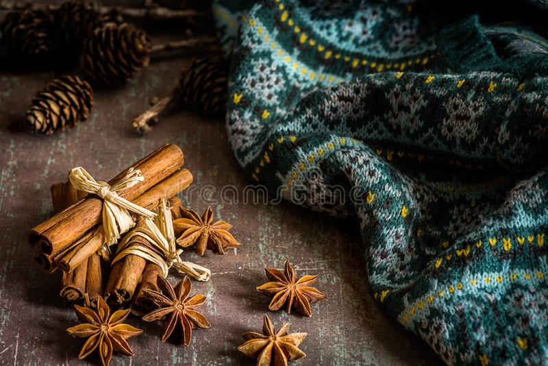 Traditional Christmas spices star anise, cinnamon sticks for fe. Christmas spices star anise, cinnamon sticks for festivity and warm knitwear on rustic stock photo