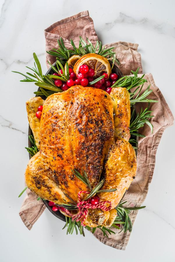 Roasted whole chicken with Christmas decoration. Traditional Christmas and Thanksgiving roasted whole chicken with fruit and rosemary. White marble background stock photo