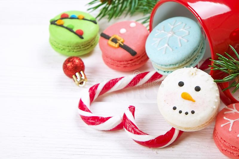 Traditional christmas themed french macaroons sweets in the form of snowman, snowflake, christmas tree and santa`s belly with cand. Y cane on the white wooden royalty free stock photo