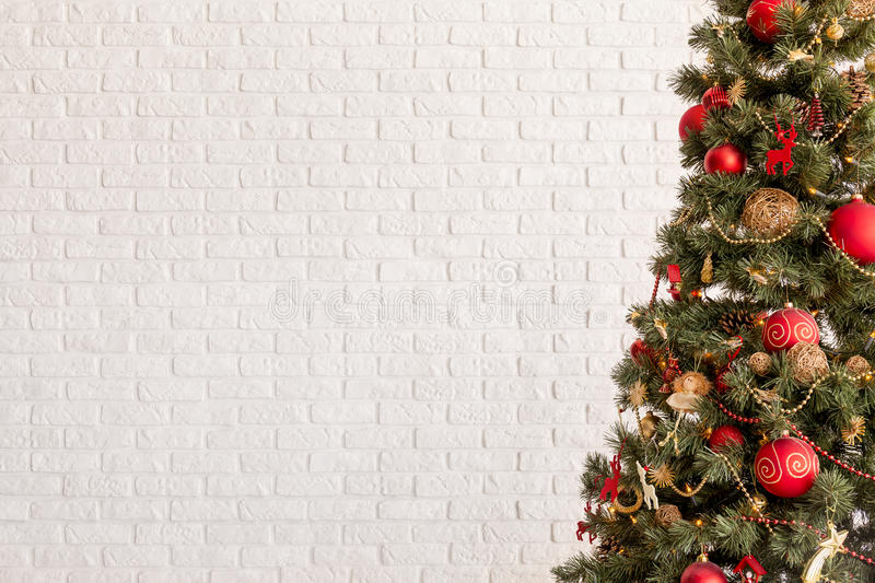Traditional Christmas tree. On a white brick wall background royalty free stock images