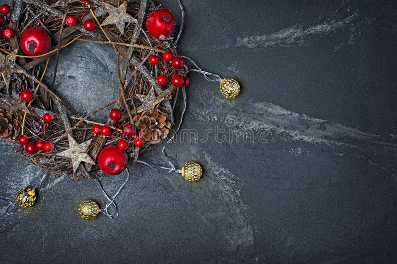 Traditional Christmas wreath from twigs with red decorations and lighted garland. Top view on traditional Christmas wreath from twigs, stars and pine cones with stock photo