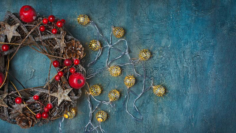 Traditional Christmas wreath from twigs with red decorations and lighted garland. Top view on traditional Christmas wreath from twigs, stars and pine cones with stock photography