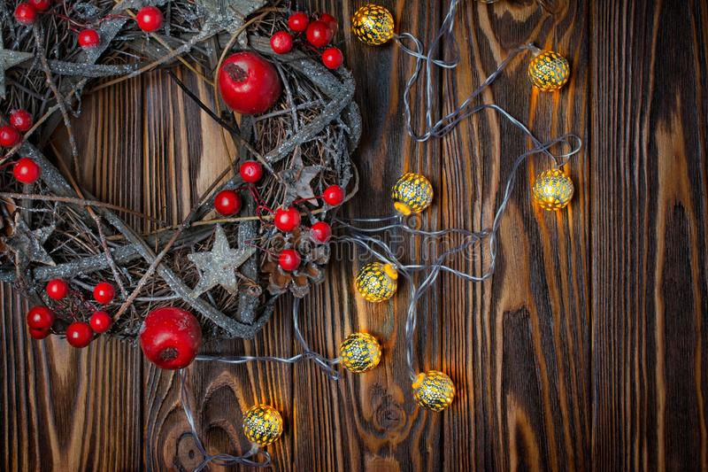 Traditional Christmas wreath from twigs with red decorations and lighted garland. Top view on traditional Christmas wreath from twigs, stars and pine cones with stock image