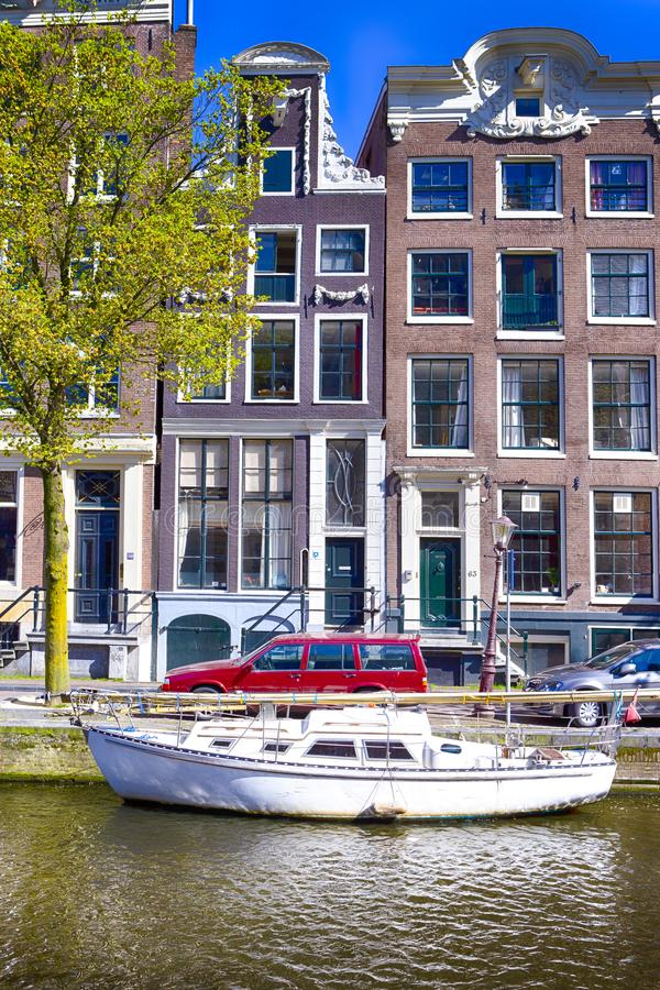 Traditional City Yacht in One of Amsterdam Canals In Front of Old Dutch Houses stock photos