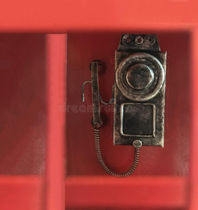 Traditional classic red phone box, in which conventional wall dial rotary phone is attached, ready to dial call. Retro furniture, royalty free stock photography