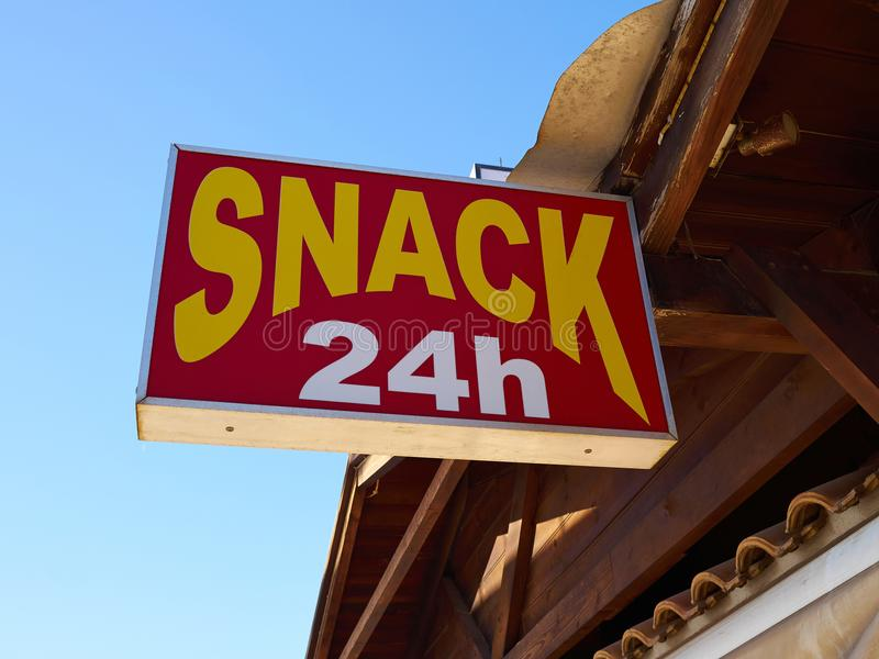 Snacks 24 hours sign hanging in front of a restaurant royalty free stock photo