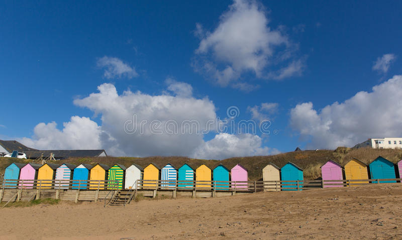 Traditional colourful English seaside scene with beach huts on the beach and blue sky with pastel colours. Of pink, blue, brown and yellow stock image