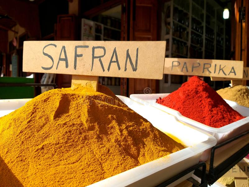 Traditional colourful spiecies in a typical exotic moroccan suk market. Saffron and Paprika writings stock photography