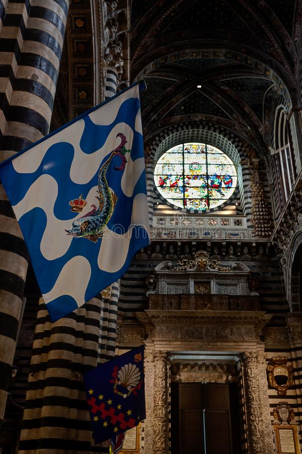 Traditional Contrada flag interior Duomo Cathedral Assumption Mary evening, Siena, Italy royalty free stock photography