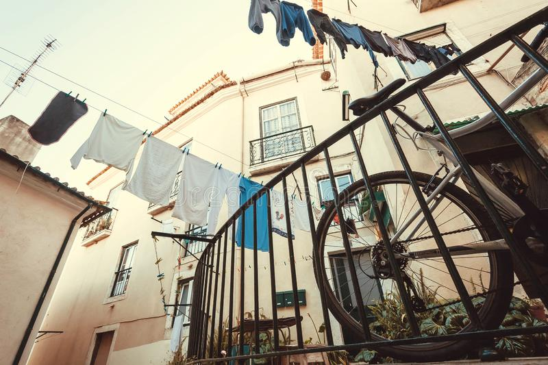 Traditional courtyard with bicycle and drying clothes over old house windows stock images