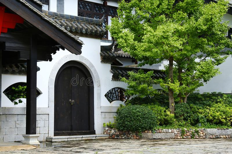 Traditional courtyard of chinese buildings. Traditional courtyard with door and tree of chinese buildings stock image