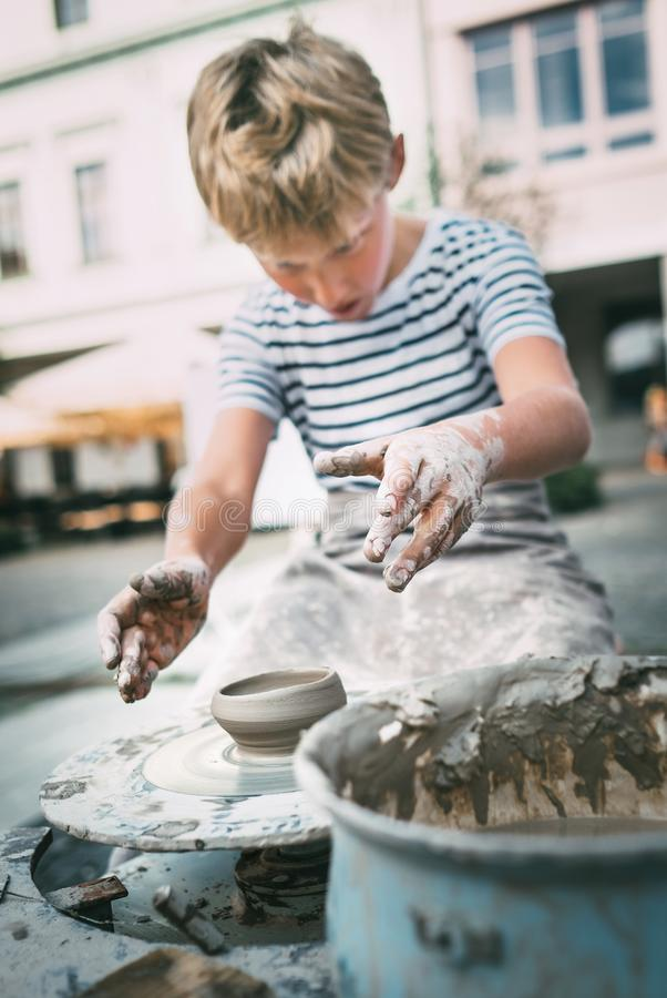 Traditional craft lesson: boy try to make a pottery bowl stock photos