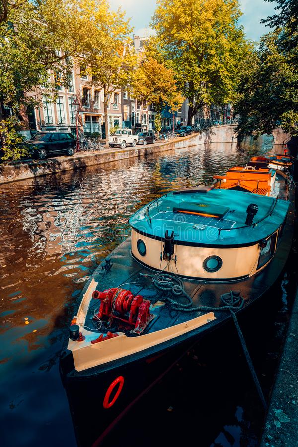Traditional cruising tour boat moored tied up in one of the famous Amsterdam canals on the beautiful, sunny autumn day.  stock photo