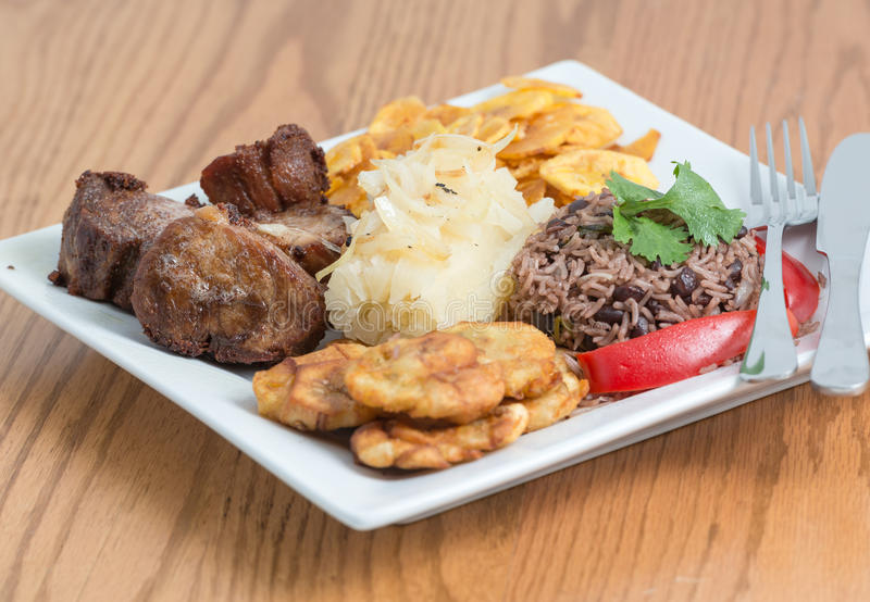Traditional Cuban Cuisine. Deep fried pork, yukka or cassava plus congri rice all with salty green banana fries. Typical Cuban Meal stock images