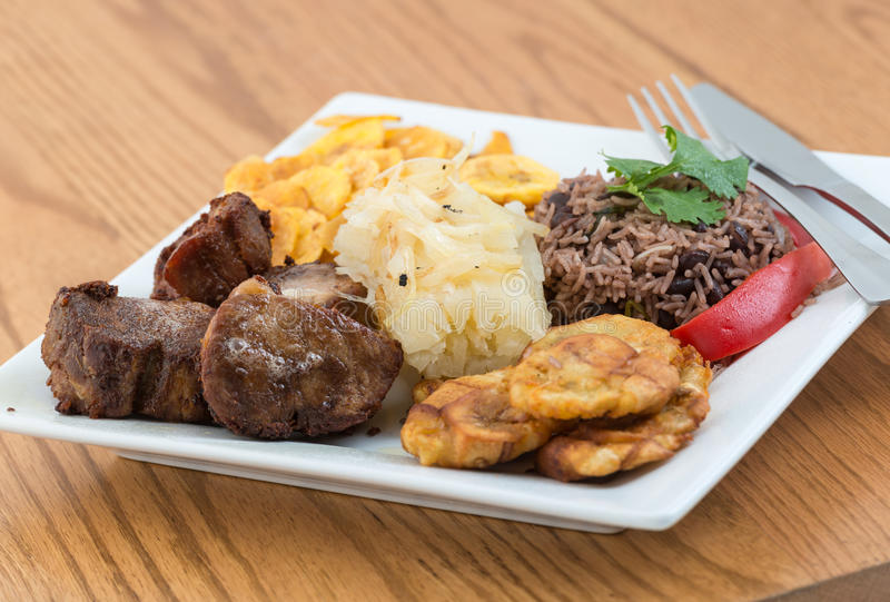 Traditional Cuban Cuisine. Deep fried pork, yukka or cassava plus congri rice all with salty green banana fries. Typical Cuban Meal royalty free stock photography