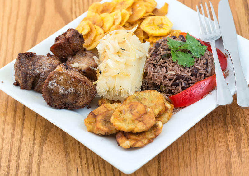 Traditional Cuban Cuisine. Deep fried pork, yukka or cassava plus congri rice all with salty green banana fries. Typical Cuban Meal royalty free stock image