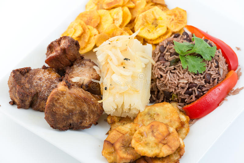 Traditional Cuban Cuisine. Deep fried pork, yukka or cassava plus congri rice all with salty green banana fries. Typical Cuban Meal royalty free stock photos