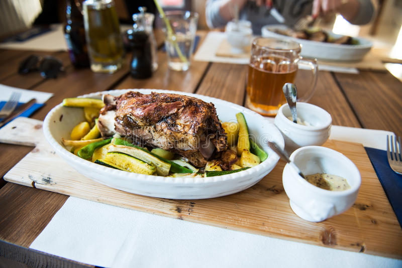 Traditional czech dinner with roasted pork leg and beer at the rataurant royalty free stock photo