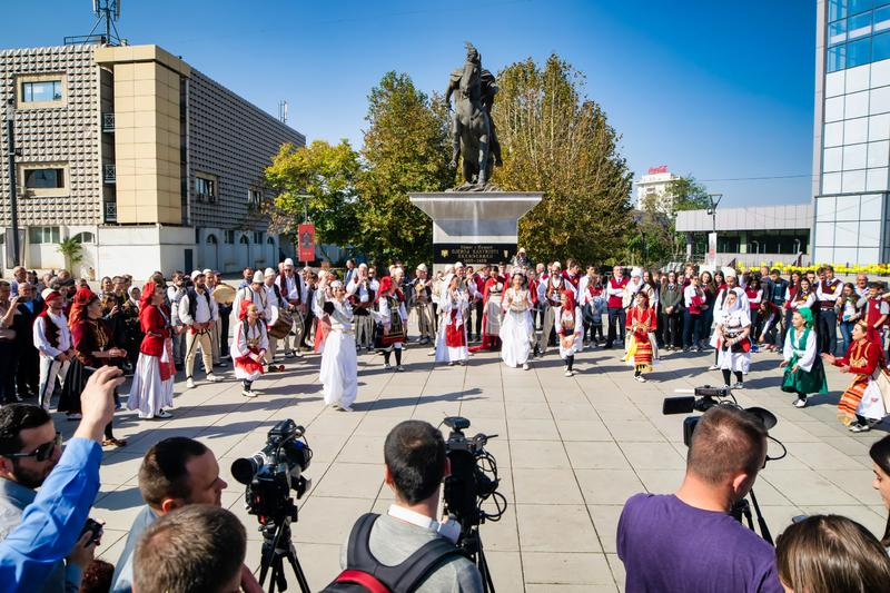 Traditional dances in Prishtina, Kosovo. Traditional dancing for people in Prishtina center in front of media and cameras amd statue on the background royalty free stock photography