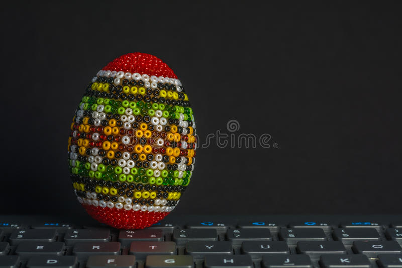 Traditional decorated Eastern egg over computer keyboard isolated on black. Traditional decorated Eastern egg over PC keyboard. Colored royalty free stock photos
