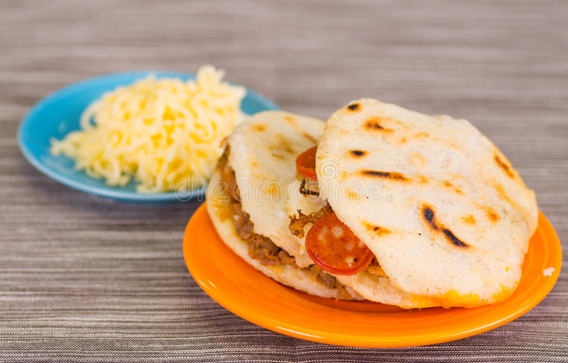 Traditional delicious arepas, shredded chicken avocado and cheddar cheese and shredded beef with grated cheese on wooden. Background royalty free stock photos