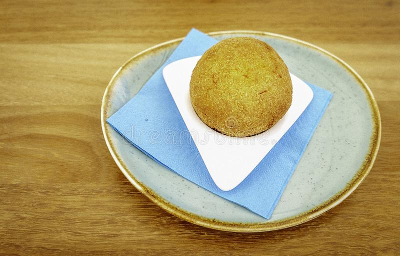 Traditional delicious Sicilian specialty arancino on a rustic ceramic dish. Traditional homemade Sicilian delicious arancino on a rustic ceramic dish and blue stock photography