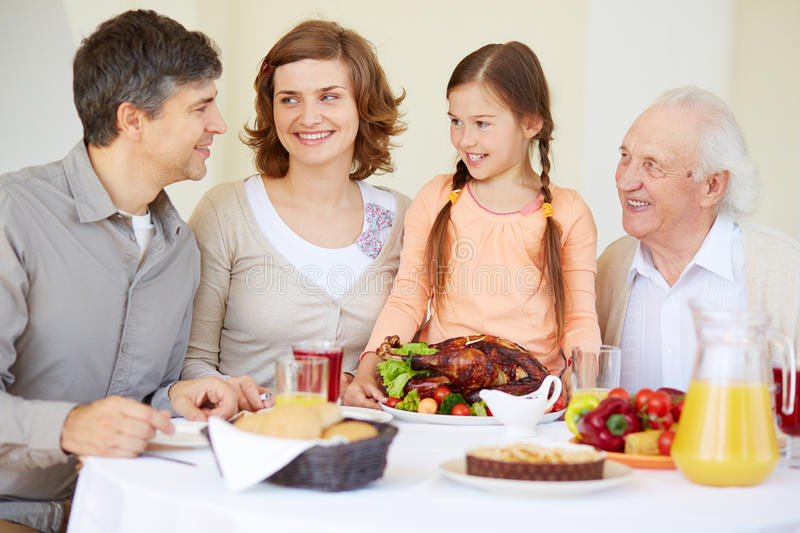 Traditional dinner. Big family looking at young men during traditional Thanksgiving dinner stock image