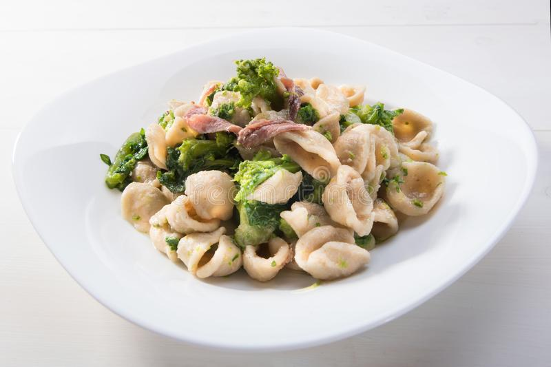 Traditional dish of Apulia region pasta Orecchiette with turnip greens and salted anchovies, top view, white wooden background. Vegetarian wholegrain Italian stock image