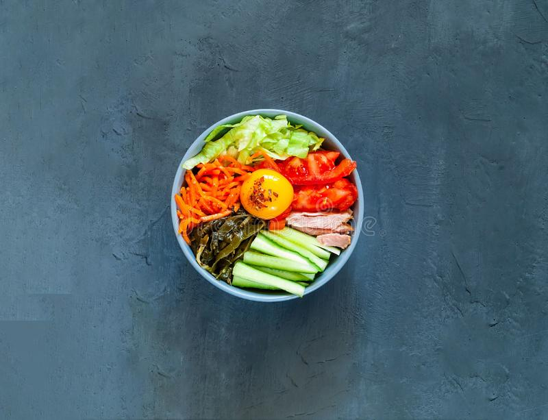 Traditional dish of Korean cuisine. Bibimbap with beef, vegetables and egg on blue background. stock photos
