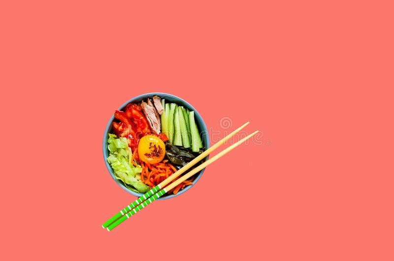 Traditional dish of Korean cuisine. Bibimbap with beef, vegetables and egg on coral background. stock images